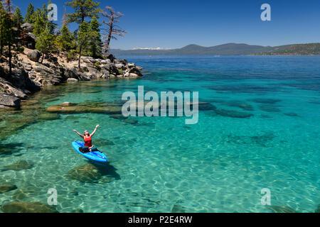 Frau Stand up Paddle Boarding auf das kristallklare blaue Wasser des Lake Tahoe in Incline Village, Nevada, Nordamerika. - Stockfoto