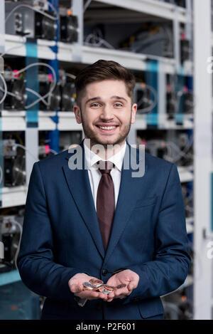 Glückliche junge Geschäftsmann mit Haufen bitcoins in die Hände am cryptocurrency Bergbau Farm - Stockfoto