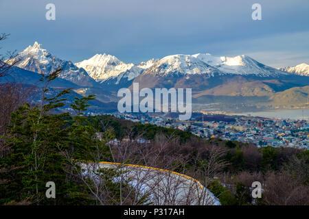 Ein Weg voller Kurven klettert über Ushuaia auf die Gletscher Martial. Hinter der Stadt, sehen sie Berge wie Monte Olivia und Monte Cinco Hermanos. - Stockfoto