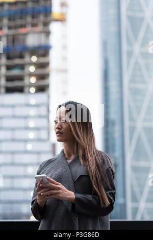 Geschäftsfrau weg schauen, während Sie Ihr Mobiltelefon - Stockfoto