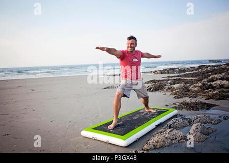 Ein Mann tut Yoga am Strand in Maine. - Stockfoto