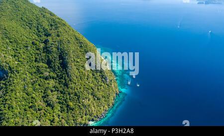 Antenne drone Blick auf die Boote im klaren Meer, über ein tropisches Korallenriff, umgeben von aufragenden Dschungel bedeckten Berge - Stockfoto