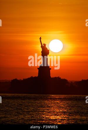 Freiheitsstatue bei Sonnenuntergang die Sonne direkt hinter sich, die einmal im Jahr passiert, - Stockfoto
