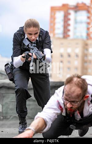 Frau Soldat, Spion agent Mörder oder Polizei Frau mit einer Waffe in der Hand, die mit Waffengewalt ein Mann auf dem Boden liegend - Stockfoto