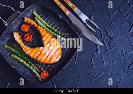 Gegrilltes Lachssteak, Spargel und Tomaten cherry am Grill zubereitet Pan Am schwarzen Stein Hintergrund mit Messer und Gabel. Gesunde Ernährung Konzept. Top vie - Stockfoto