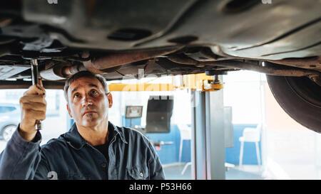 Erfahrene Automechaniker Instandsetzung einer angehobenen Auto in der Garage. Auto Reparatur Männer Befestigung auspuffanlage von einem Auto. - Stockfoto