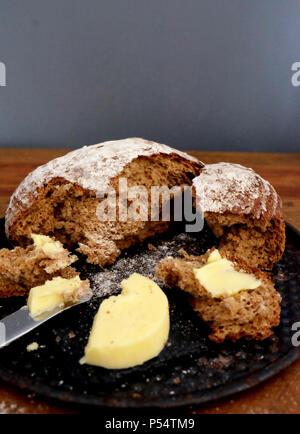 Kreisförmigen braunes Brot auseinander mit ein paar Brocken auf einem Brot und hölzernen Tischplatte Butter und Messer, Messer hat Butter auf es bereit für spre - Stockfoto