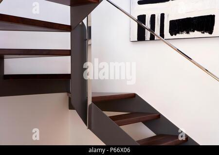 Holztreppe mit Gemälde an der Wand und Edelstahl Handlauf - Stockfoto