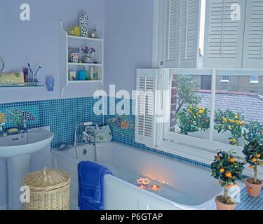 Schwimmende Kerzen in der Badewanne unter Fenster mit weißen Fensterläden in blau Badezimmer mit blauen Mosaikfliesen - Stockfoto