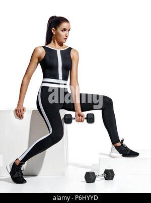 Sportlerin führt Übungen mit Hanteln für die Hände. Foto von Latin girl in modischer Sportbekleidung auf weißem Hintergrund. Stärke und Moti - Stockfoto