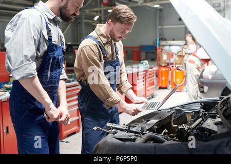 Zwei Mechaniker Inspektion Auto - Stockfoto