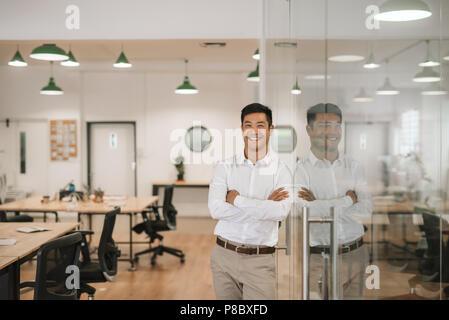 Lächelnd asiatische Geschäftsmann gegen eine Glaswand bei der Arbeit schiefen - Stockfoto