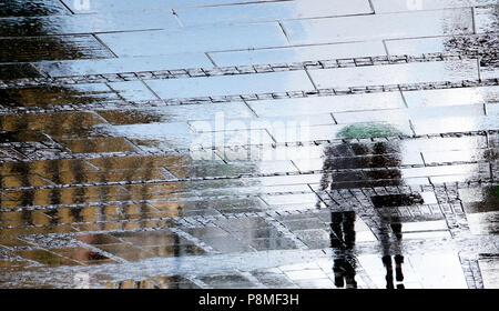 Unscharfe Reflexion Schatten Silhouetten, die laufen an einem regnerischen gemusterten Stadt bürgersteig an einem Frühlingstag - Stockfoto