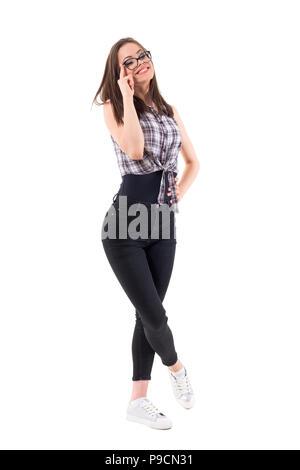 Gerne fröhliche hübsche Teenager Frau berühren Brille lächelnd und mit Blick auf die Kamera. Voller Körper auf weißem Hintergrund. - Stockfoto