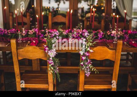 Hölzerne Hochzeit Tisch mit roten Kerzen, rosa Tuch und lila Orchideen eingerichtet. Romantische Abendessen mit der Familie am Abend - Stockfoto