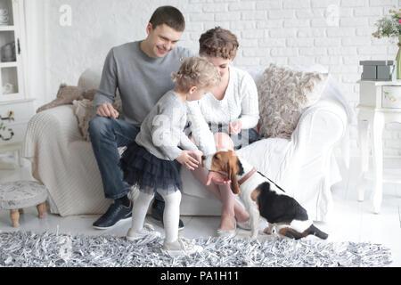 Glückliche Eltern bei ihrer Tochter, die füttert den Hund suchen - Stockfoto