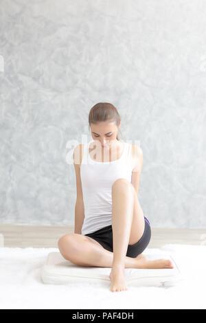 Junge kaukasier sehr attraktiven Frau Üben Yoga, sitzen in Padmasana Yoga Übung oder Lotus Pose oder Namaste darstellen. Sie arbeiten an Ihrem Bett. - Stockfoto