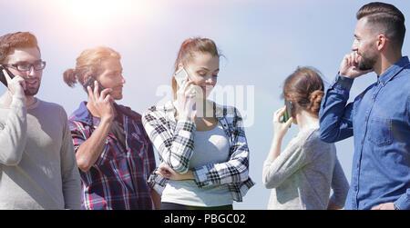Junge Menschen sprechen auf ihren Smartphones. - Stockfoto