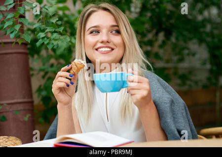 Ziemlich lächelnde Mädchen essen croissant Sitzen mit Schultern mit warmen gemütlichen grau Decke abgedeckt. Die Tasse Kaffee, lesen Buch, tragen weiße Bluse mit Perlen verziert, auf der Seite suchen. - Stockfoto