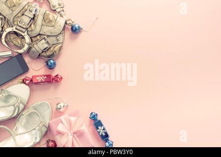 Weihnachten Hintergrund rosa Flach Mode Accessoires Handtasche Sandalen Telefon Geschenk Box bug Kugeln. Ansicht von oben kopieren Raum - Stockfoto