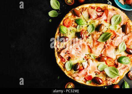 Blick von oben auf die lecker appetitlichen klassische italienische Pizza mit Käse, Oliven, Basilikum und frisches Gemüse auf dunklen schwarzen Tisch. - Stockfoto