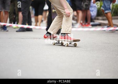 Jugendlich Skater Boy reitet auf Skateboard outdoor. Extreme Sommer skaten Wettbewerb für junge und aktive Sportler. Füße der Skateboarder in Rot skater Schuhe - Stockfoto