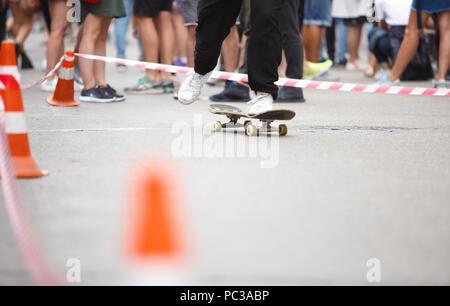 Füße von jungen Skater Boy reiten auf Skateboard im Freien im Sommer. Extreme Sport Wettbewerb Hintergrund. Ride Skate Board für Spaß - Stockfoto