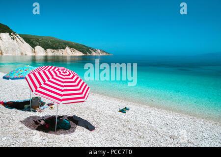 Sun Sonnenschirme auf einem Kieselstrand mit azurblauen Meer, weiße Felsen und klaren Himmel im Hintergrund. - Stockfoto