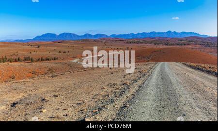 Schotterstraße, die sich durch die Haare orange Hügel in die Berge in Ikara-Flinders Ranges National Park, South Australia - Stockfoto