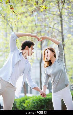 Glückliche junge chinesische Paar tun Herzform Geste - Stockfoto