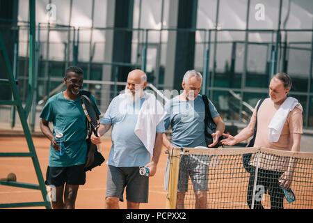 Portrait von lächelnden multirassischen ältere Freunde mit Tennis Ausrüstung auf Gericht - Stockfoto