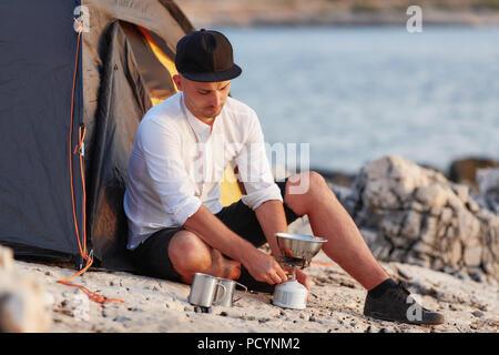 Junge Mann sitzt auf felsigen Küste in der Nähe von Zelt, Einstellung gas Kachel. - Stockfoto