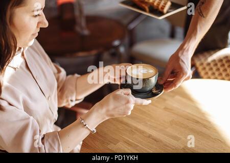 Angenehme Frau nimmt ihren Kaffee im Restaurant. Das Frühstück Konzept. top View - Stockfoto