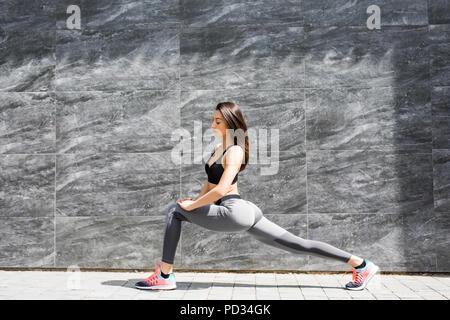 Stilvolle attraktive junge Läuferin in schwarz Sportswear tun Warmlaufroutine draußen vor der Ausführung, Stretching Beine mit ausfallschritt Oberschenkelmuskeldehnung - Stockfoto