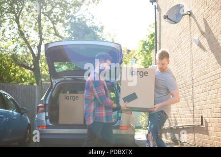 Männliche homosexuelle Paare entladen Kisten aus dem Auto - Stockfoto