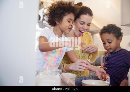 Verspielte Mutter und Kinder backen in der Küche - Stockfoto