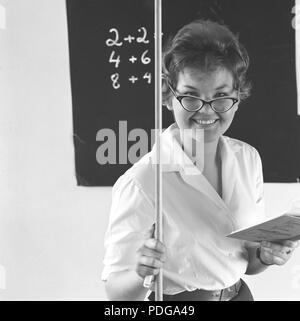 1950er Schullehrer. Eine junge Frau stellt sich als ein Mathelehrer und steht vor der Tafel, wo ein paar Zahlen geschrieben werden. Sie lächelt und hält eine Holz- Zeiger in der einen Hand und eine Schule Buch in der anderen. 1958 Sverige 1958 - Stockfoto
