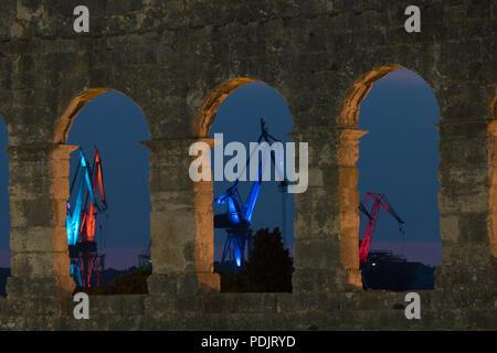 Rovinj, Kroatien - 31. Juli 2018: Die Nacht der Blick durch die Bögen der Amphitheater von Pula auf die beleuchtete Hafenkrane der kroatischen Stadt. - Stockfoto