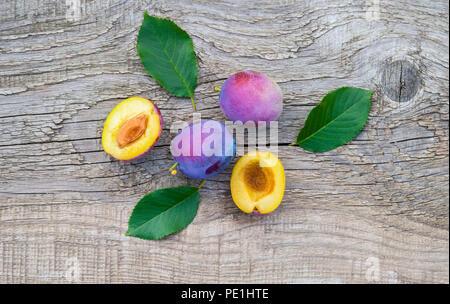Reife Pflaumen mit Blättern auf alten hölzernen Hintergrund - Stockfoto