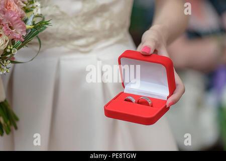 7/8 shot der kaukasischen Frau, hält ein Schmuck Red Box mit passenden Silber oder Platin Trauringe, in der Vorbereitung für eine Hochzeit - Stockfoto