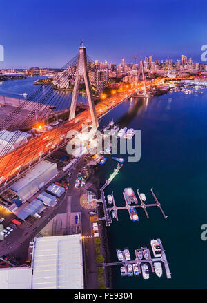 Stadt Sydney ANZAC Bridge am Hafen während der Blauen Stunde in Antenne erhöhten Blick auf City Marina in Richtung CBD Türme mit helle Beleuchtung. - Stockfoto