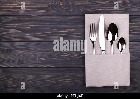 Satz von Gabel, Löffel, Teelöffel und Messer mit Bettwäsche Serviette auf Holztisch. Ansicht von oben. - Stockfoto