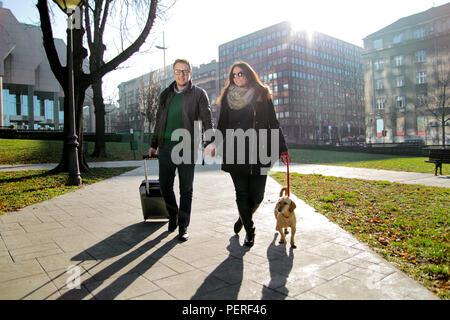 Paar mit Koffer und Hund Fuß in den Park am frühen Morgen. Glückliches junges Paar zu Fuß durch den Park mit niedlichen Hund und genießen. - Stockfoto