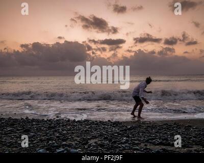 Model Released Bild eines teenaged Jungen skimming Stones in der Abenddämmerung am Strand - Stockfoto