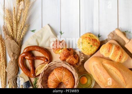 Hausgemachtes Brot oder Brötchen, Croissant und Backzutaten auf weißem Holz Hintergrund, Frühstück essen Konzept top Ansehen und Kopieren Raum - Stockfoto