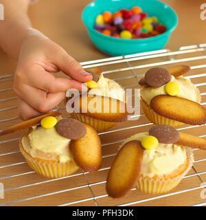 Die Mädchen Hand dekorieren Cupcakes mit Süßigkeiten, close-up - Stockfoto