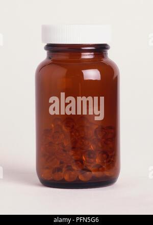 Braun Glas Glas zur Hälfte mit Pillen gefüllt. - Stockfoto