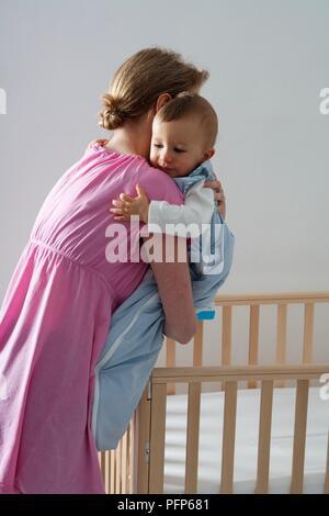 Frau mit baby boy bereit, ihn im Babybett zu platzieren, Seitenansicht - Stockfoto