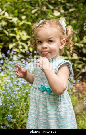 18 Monate altes Mädchen, ein lustiges Gesicht nach Essen einige Forget-Me-Not Blumen (MR) - Stockfoto
