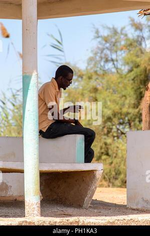 DJOUDJ, SENEGAL - Apr 25, 2017: Unbekannter senegalesischen Mann sitzt an der Grenze von der Bushaltestelle in Djoudj, beliebte touristische Destination - Stockfoto
